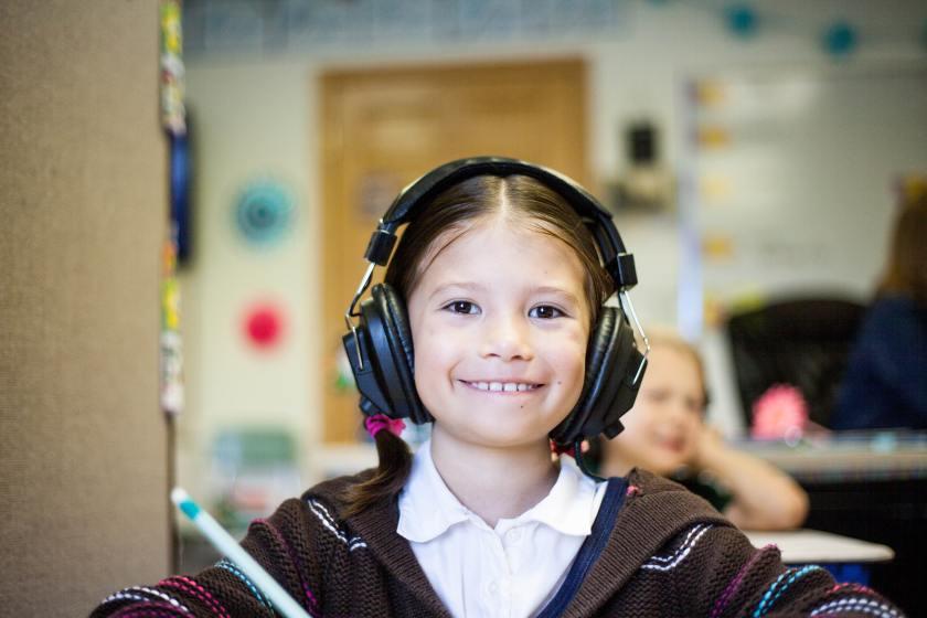 Nuori hymyilevä tyttö jolla isot kuulokkeet päässä.