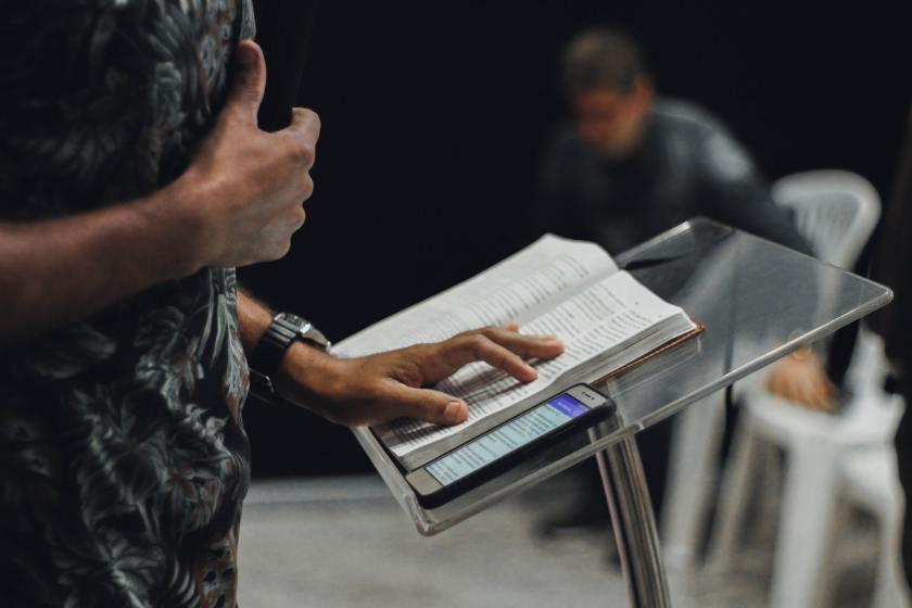 Lukija lukee kirjaa joka on telineella. Vieressä kännykkä