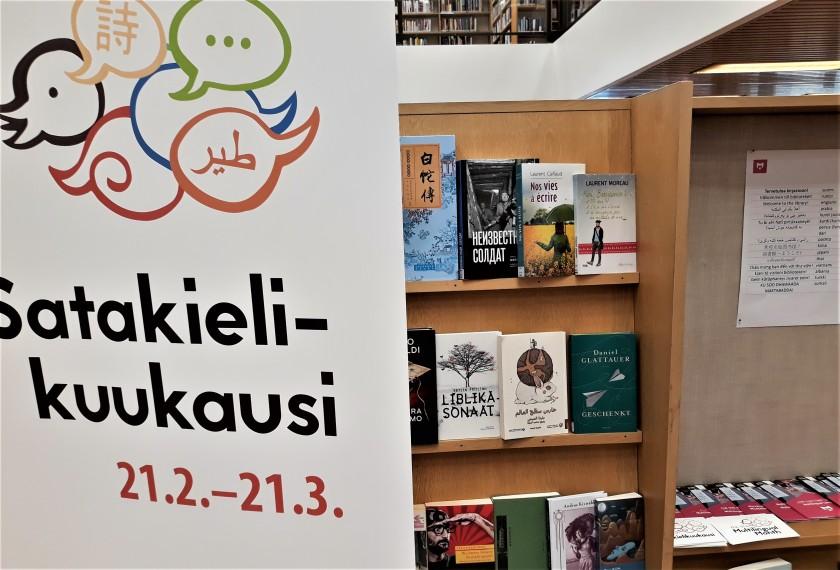 Satakielikuukausi rollup ja monikielisiä kirjoja hyllyssä.
